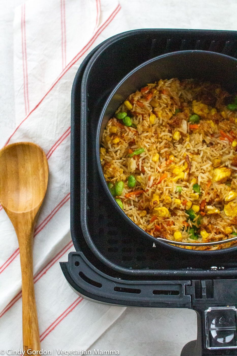Air Fryer Fried Rice in air fryer basket with wooden spoon