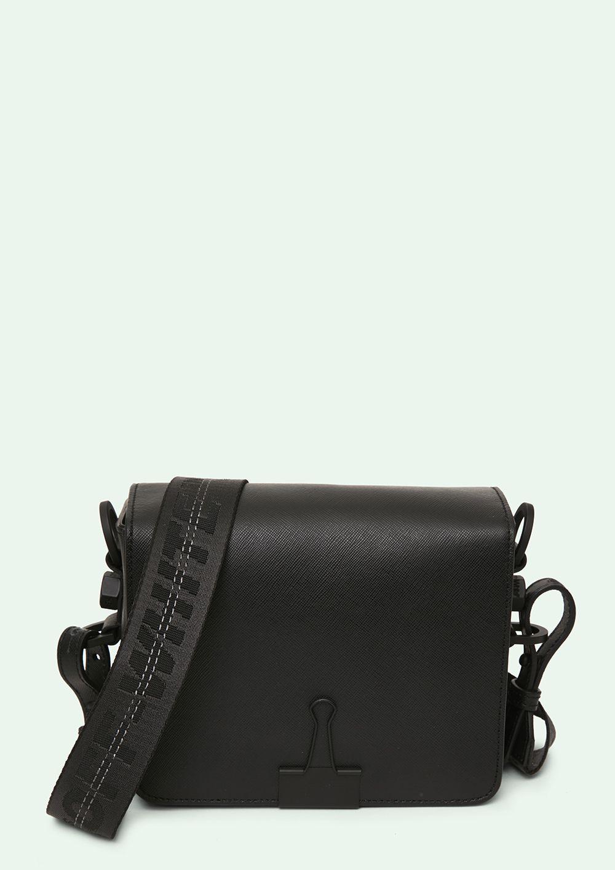 "Cross body leather flap bag in black with black ""TIE DOWN"" Industrial belt strap. ""SCULPTURE"" print at back. Height 17cm. Width 19 cm. Depth 10 cm. Width shoulder strap 7 cm. Length ""TIE DOWN"" shoulder strap 162 cm."
