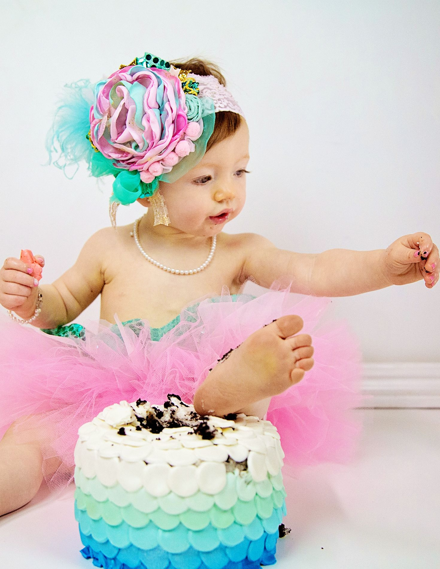 Mermaid smash cake first birthday photo session.  I love her real pearl necklace (all mermaids need pearls), under the sea ombre cake, her pink & green tulle tutu and her amazing baby flower headband!  So cute!   Take a peek at all of our fun first birthday smash cake photo props from Little Girl's Pearls! ♥