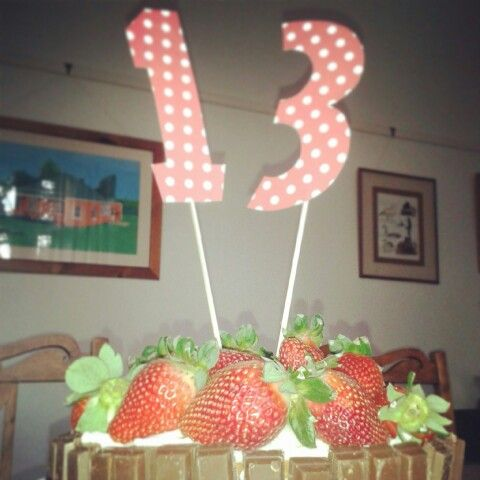 Vanilla cake decorated with whipped cream,  strawberries and kit-kats.