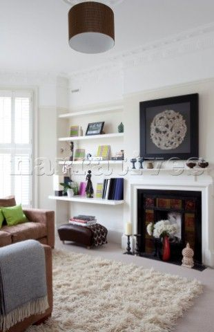 living room ornaments furniture images on shelving next to fireplace in white of contemporary london home uk