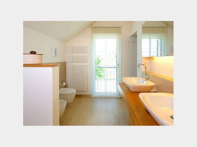 Ein Badezimmer Mit Durch Halbhohe Wände Abgetrennten WCs Und Warmem Licht  Unter Dem Spiegel Wirkt Elegant