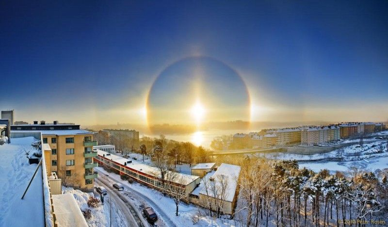 Ice crystals  act like a miniature lens, refracting sunlight into the halo view