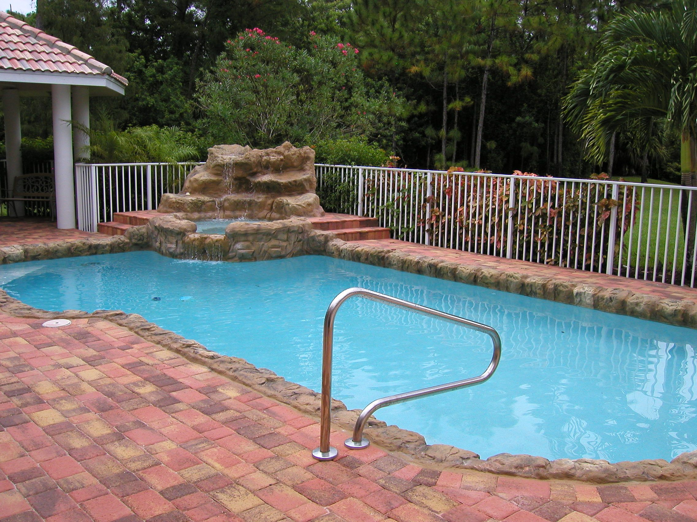 Custom Free Form Pool Rock Waterfall White Aluminum Rail Fence Brick Paver Deck And Handrail Pool Builders Custom Pools Swimming Pool Construction