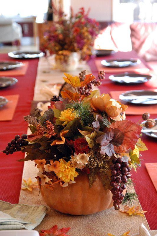 red tablecloth, orange place mats, natural table runner, white candles, pumpkins vase, flower arrangements