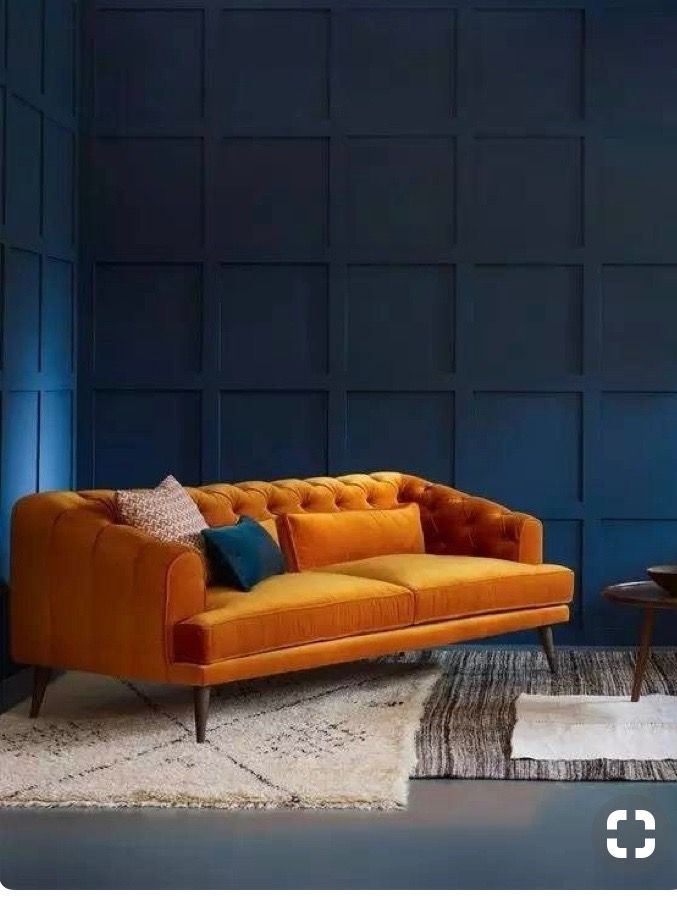 Dark blue wall pannels with orange velvet sofa home - Burnt orange feature wall living room ...