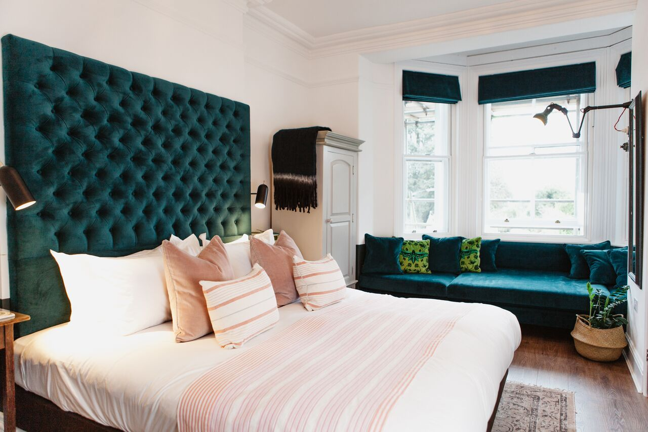 A bespoke day bed in green velvet under a window with a