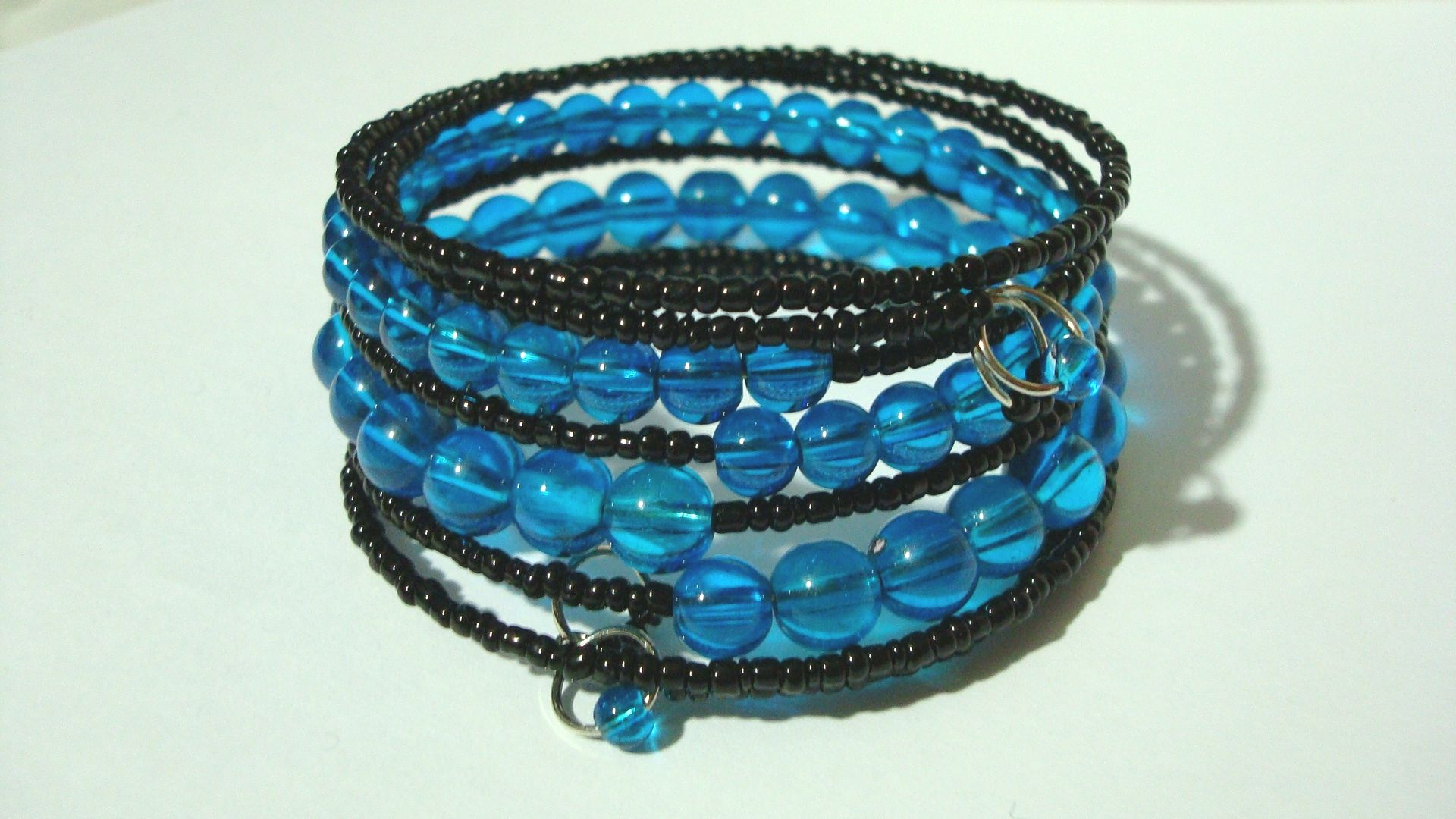 """http://www.etsy.com/listing/107862462/memory-wire-multistrand-blue-and-black    - Memory Wire Multistrand Blue and Black Glass Bangle Bracelet    - Aprox. 2.5"""" x 2.5""""    - Stainless steel memory wire... adjusts to fit all    - Please see pictures."""