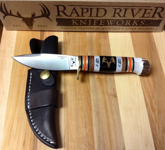 Rapid River Knifeworks Custom 1 of 1 Drop Point (with False Grind) Hunting Knife This knife has a beautiful handle, featuring a bison horn in the center (black) with deer antlers laser engraved into it, deer antler pommel, stacked leather & bright hunter orange micarta spacers. A truly unique hunting knife!