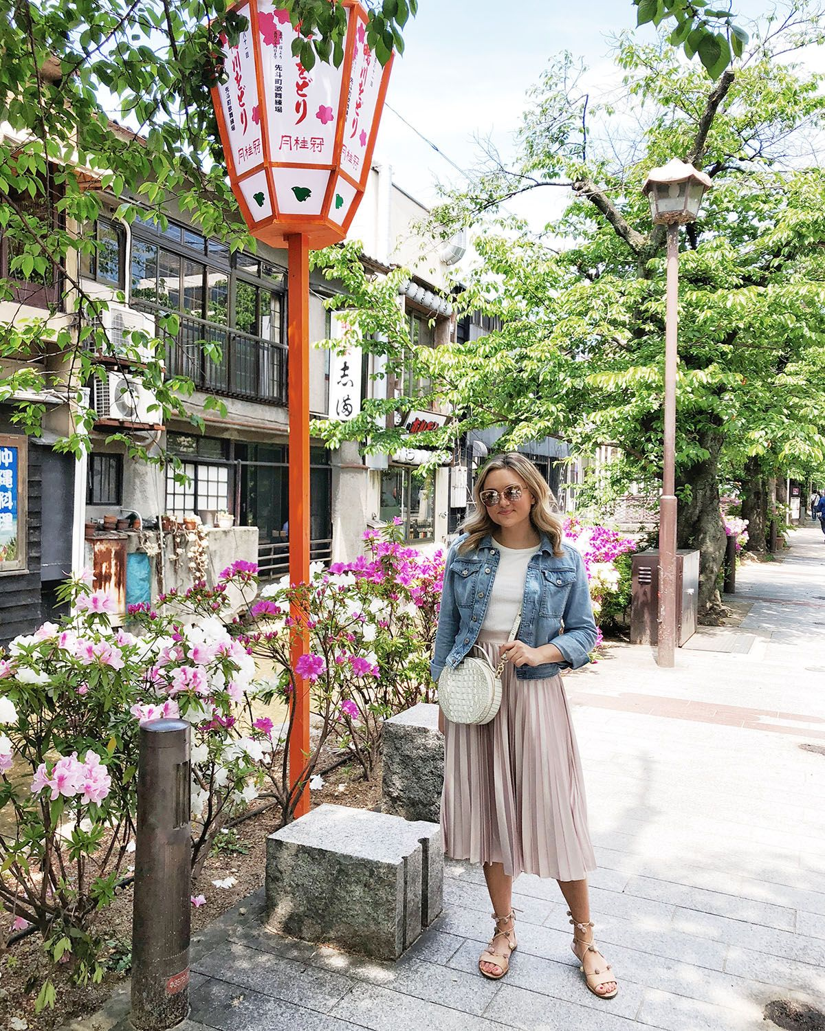 f32ed21cd9 Bows & Sequins Travel Guide in Kyoto Japan. Jessica Sturdy is wearing a denim  jacket, pink pleated midi skirt, a Brahmin circle handbag, and Loeffler ...