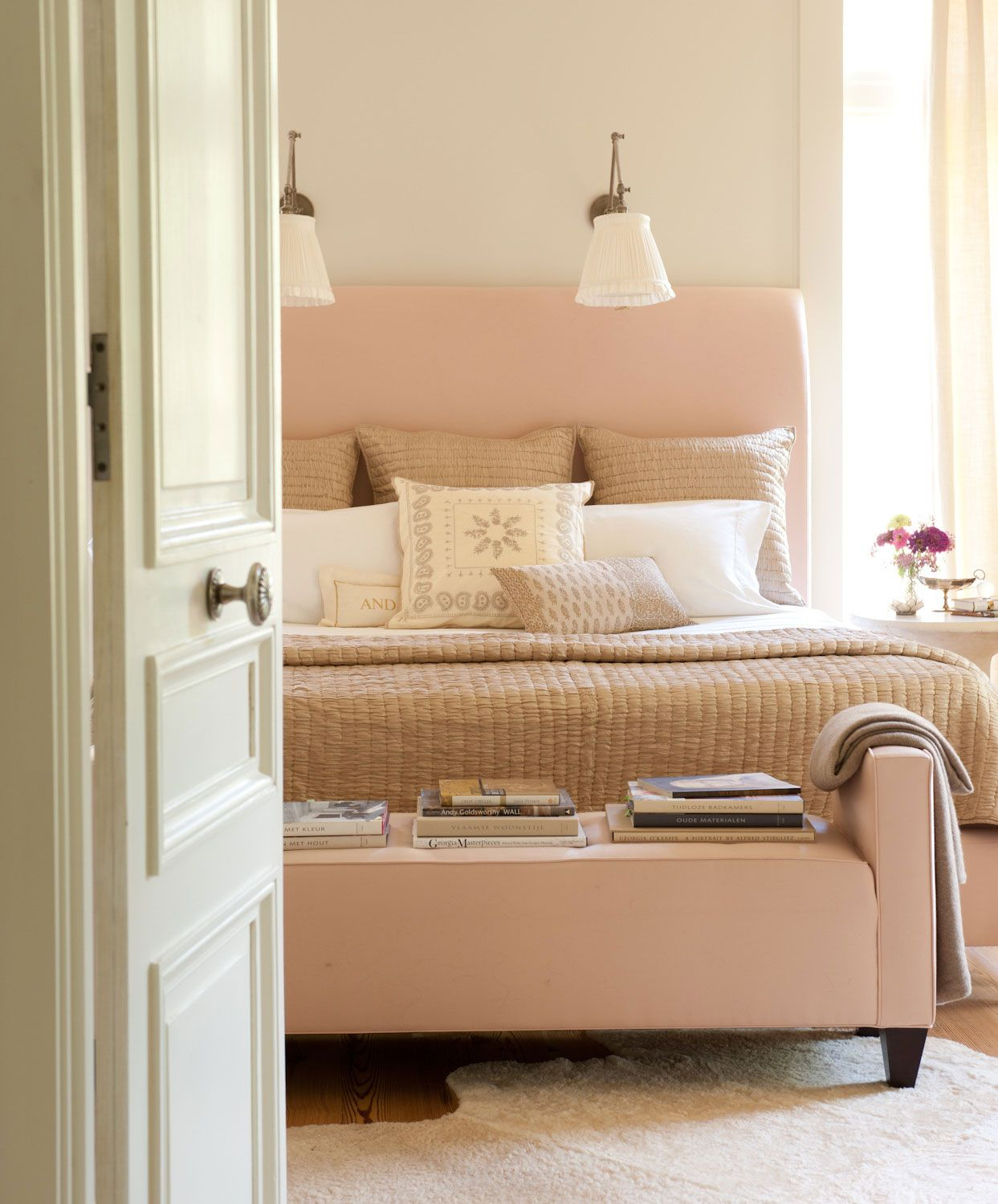 Blush master bedroom design with matching foot bed bench seating