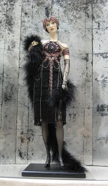 Denise Art Deco doll by Alexandra Koukinova    Biscuit porcelain.   Antiquarian laces with hand beadwork and silver thread.  Skirt is made of hand beaded fringe.   Ostrich boa. Jewelry – silver with semiprecious stones.   Antiquarian beaded threads are used in dress and headdress décor.  Hand painting.  LE 4, 23 inches tall (25 inches with a feather).