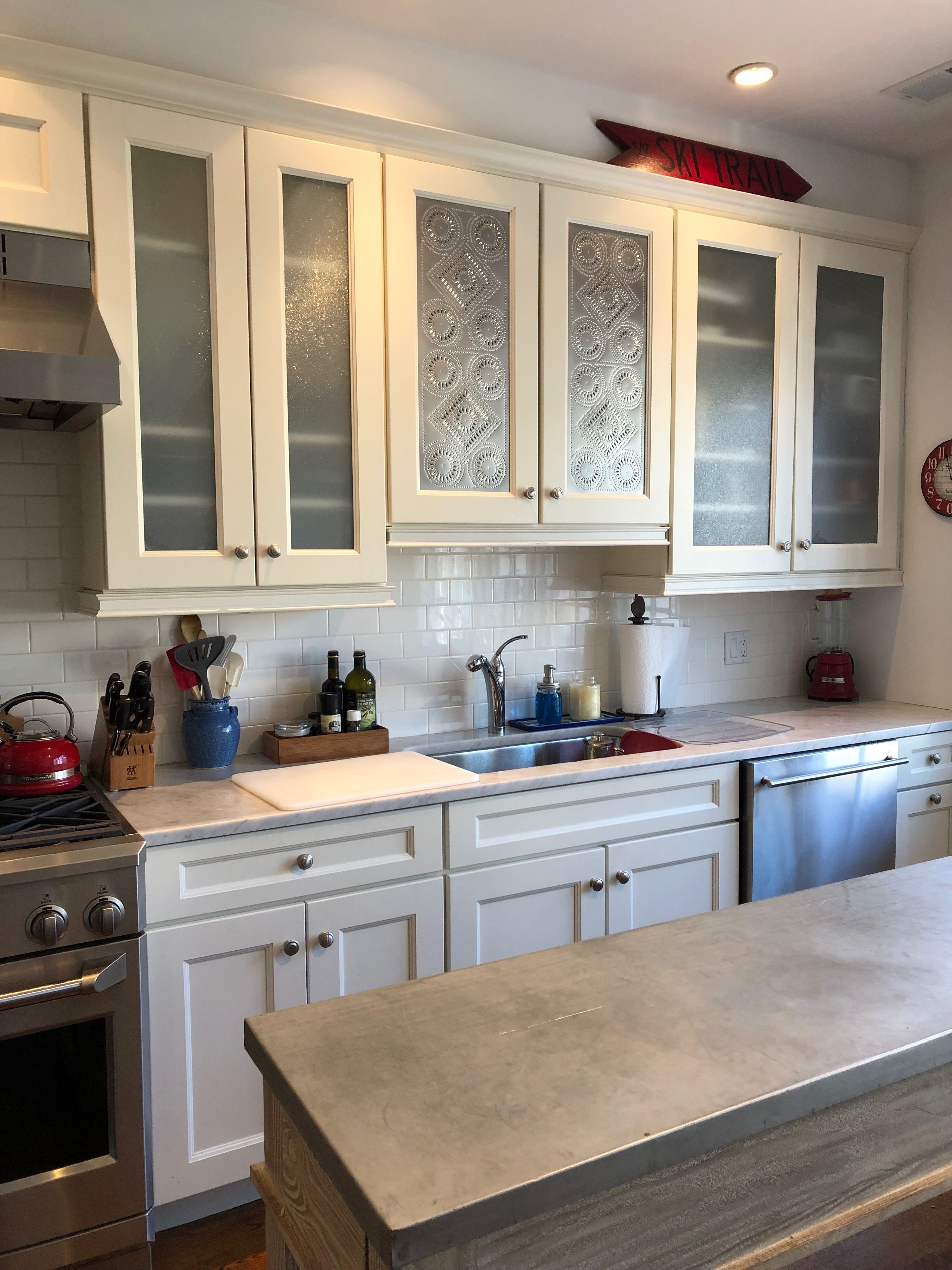 Using Pierced Tin Panels To Add A Bit Of Farmhouse Style To An Otherwise Bland Builder S Kitchen Kitchen Cabinets Tin Panel Kitchen