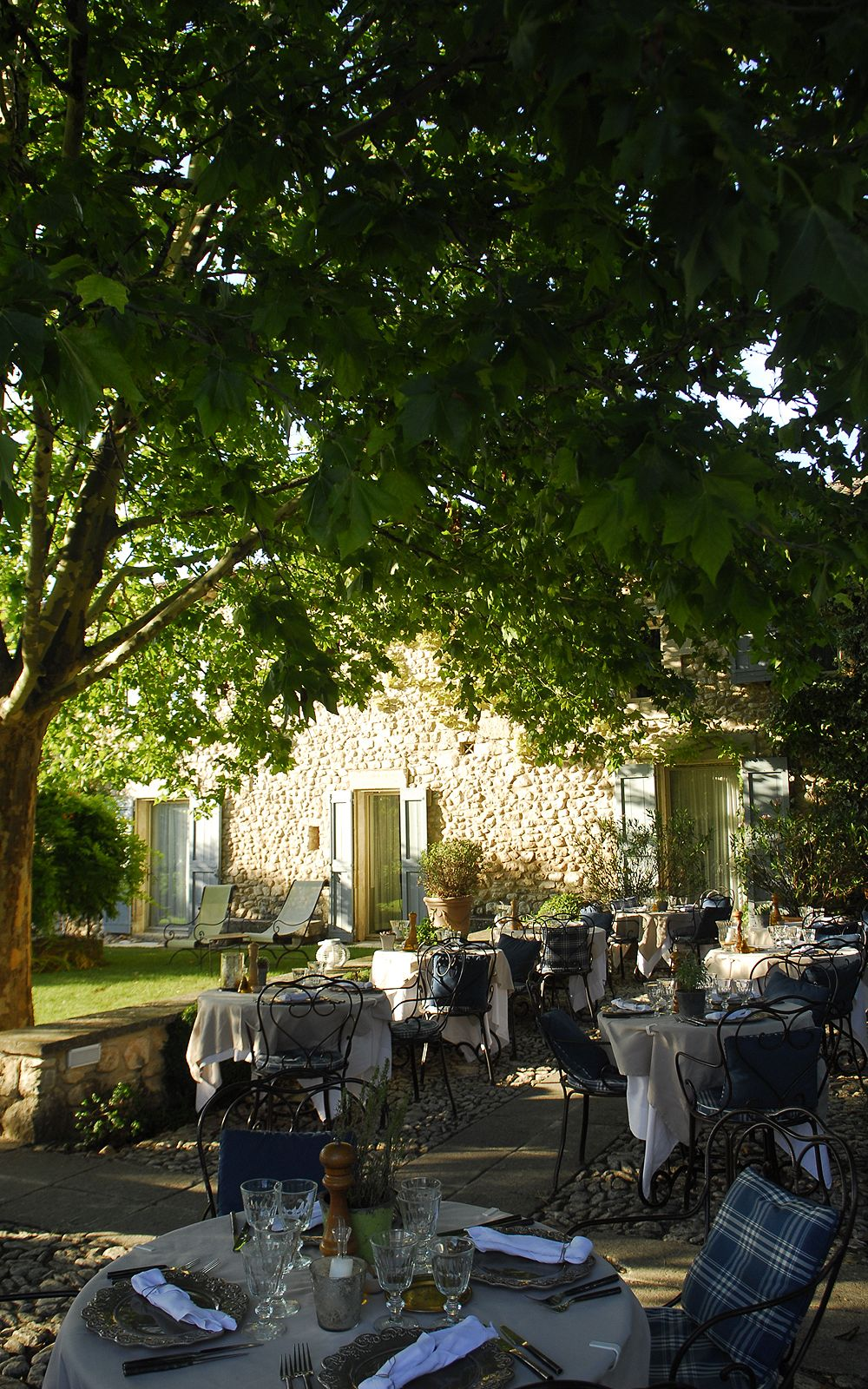 La Bastide de Marie. Gravel terrace. Big trees. Lawn. Stone. Shutters. Sunlight. Wrought iron furniture.