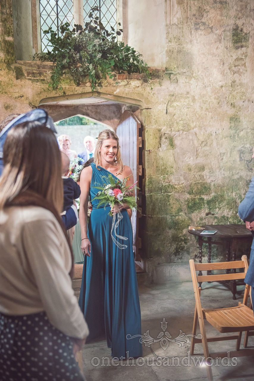 Bridesmaid In Green Greco Roman Dress Leads Wedding Procession At Church Photography By