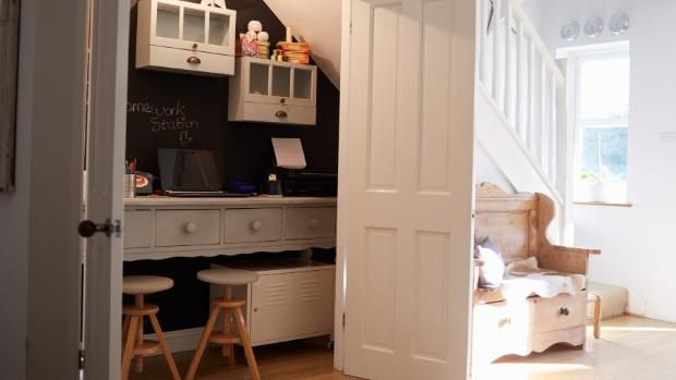 How to create a workable home office in a small space.    Wasted space under the stairs is converted into a home office, and the doors can be closed to hide the mess.