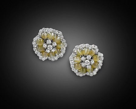 """This stylish pair of earrings from the renowned Neiman Marcus features an incredible 12.75 carats of lustrous Chrysoberyl """"cat's-eye"""" cabochons set amid approximately 3.00 carats of sparkling round-cut diamonds. Set in 18K white gold Omega-backed posts in an elegant floral motif, these excellent and eye-catching gems allow light to both dance and glow in a delicate balance. Chrysoberyl cat's eyes are genuine rarities that are found only in a few deposits in the world. Regarded as a…"""