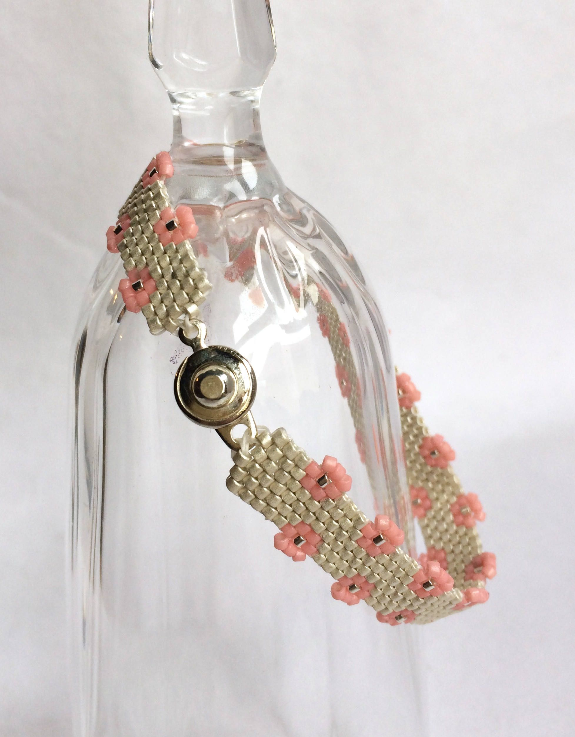 This handcrafted, needle beaded cuff bracelet is done in Peyote stitch in silver with a pink flower edging. It is 7 inches long and 1/4 inch wide with a silver plated snap clasp. The bracelet is easy to wear, easy to put on and take off, and is a delightful addition to your summer wardrobe. The silver band is made with sterling silver plated glass beads which gives it a bright silver sheen; and the pink flowers add sweetness to the elegance of the cuff. It is a perfect summer addition to...