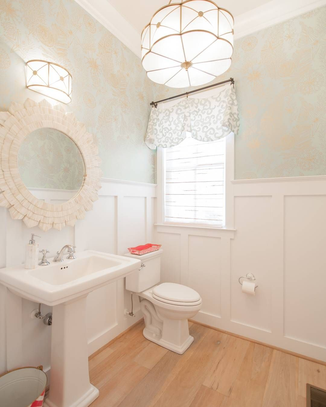 This powder room features a subtle combination of #boardandbatten #wainscotting and wallpaper. Wide plank floors brings warmth while stunning lighting adds some glamour to this space. #whatsnottolove See more #pics and #sources on the #blog #today homebunch.com Design by Strickland Homes.  #interiordesignblog #Interiordesigner #interiors #interiordesign #beautifulhomes #homes #homeideas #whotofollow #follow #turquoise #beachhouse #coastalinteriors #justnow #newpic #houses