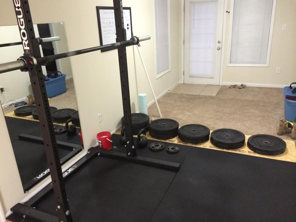 A simple clean garage gym with barbells and bumper plates garage