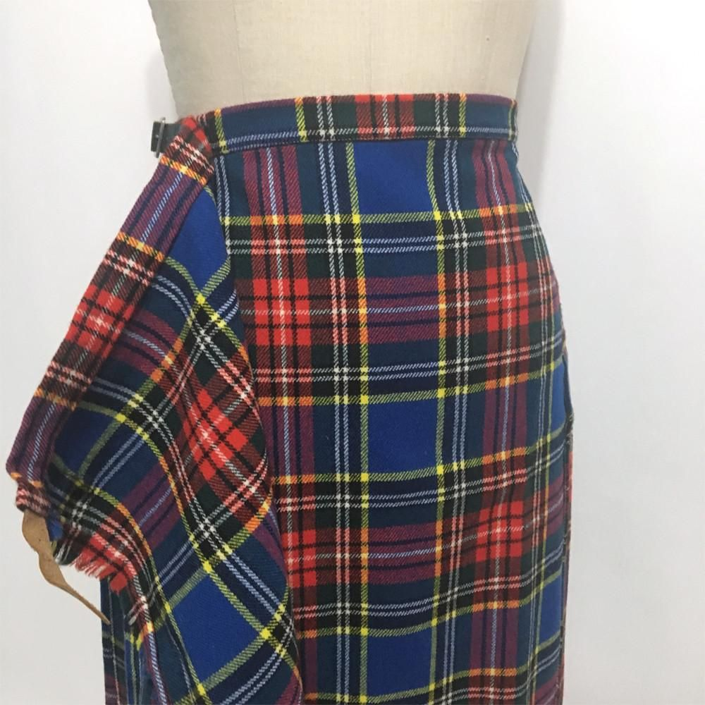45559f56f70e Pleated wrap skirt overlaps in from with buttons and a leather belt tabs  with buckles. TAG Aston London, New York MATERIAL 100% wool ...