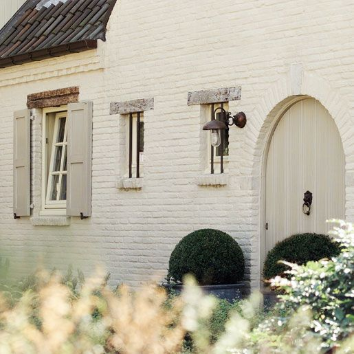 I love.....LOVE... white painted brick.. not to mention the rounded arch door..and the shuttered windows... with shutters that actually work as you can tell from the framing above and below the windo.. so nice..