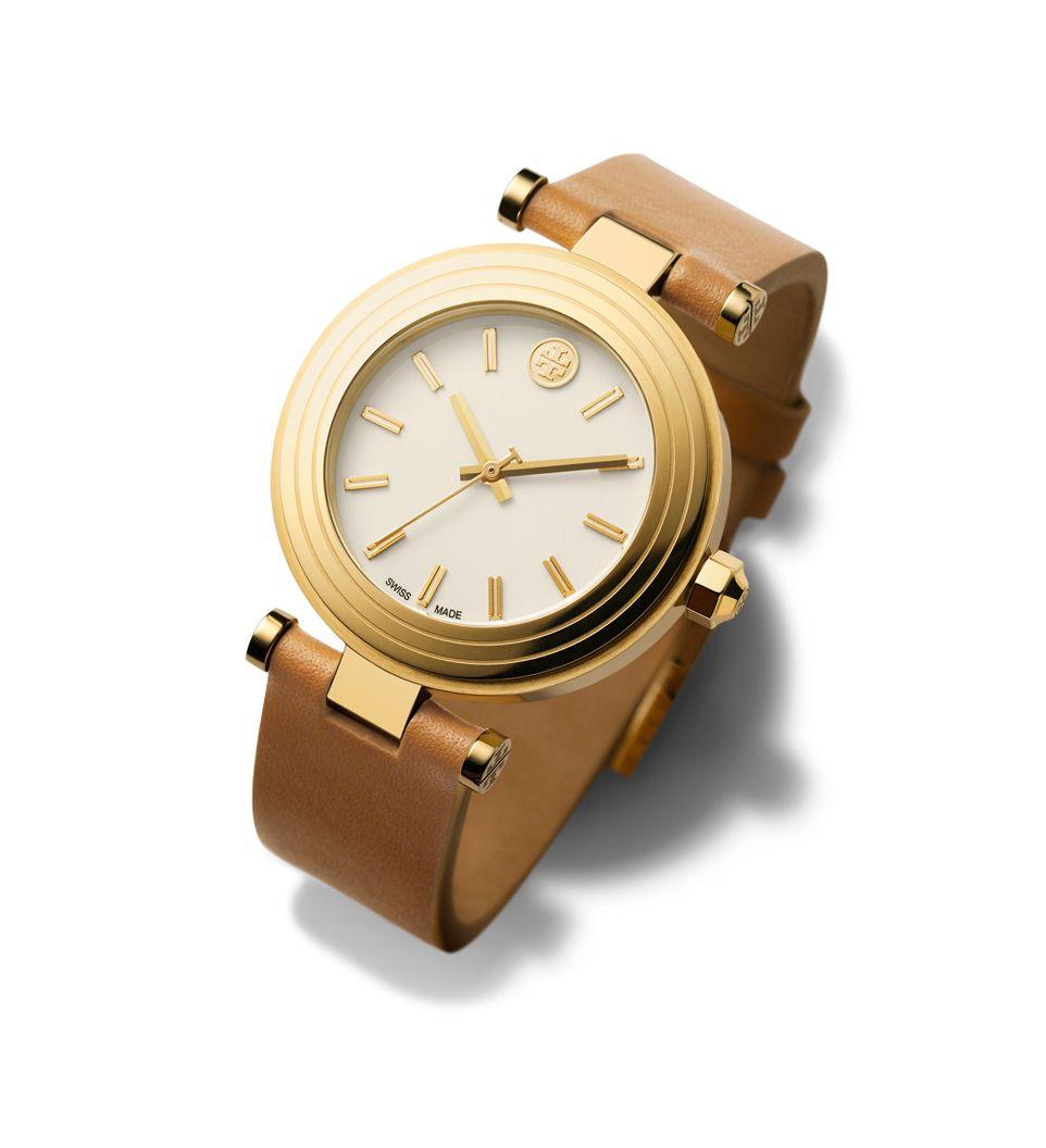 En lekker klokke fra Tory Burch. Modellen er en mix av moderne og klassisk stil, og kommer i gullfarget rustfritt stål med en brun italiensk skinnrem.