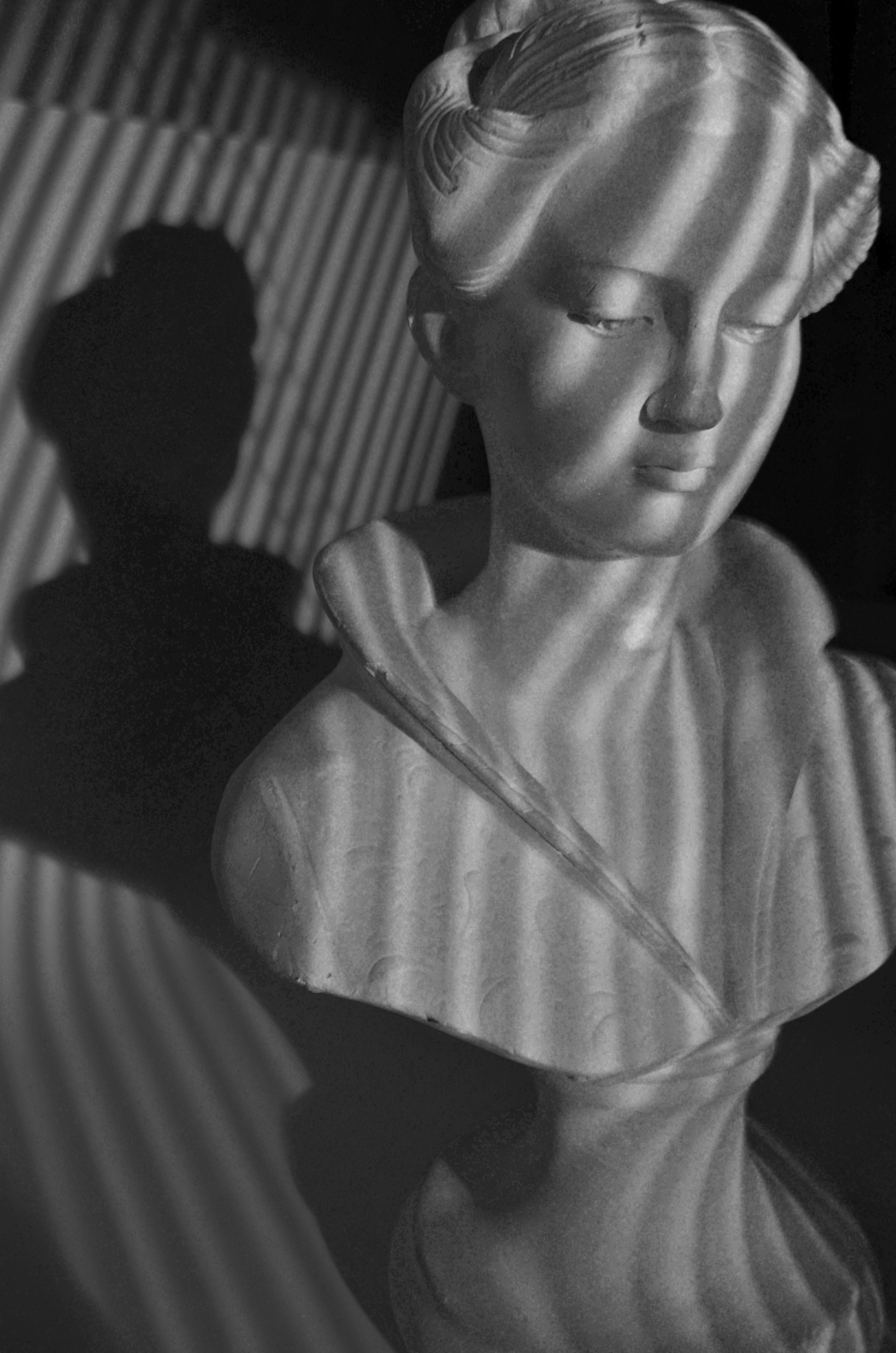 Still life shot of a statue that demonstrates excellent shadow lighting with the use of curves in background and statue itself.
