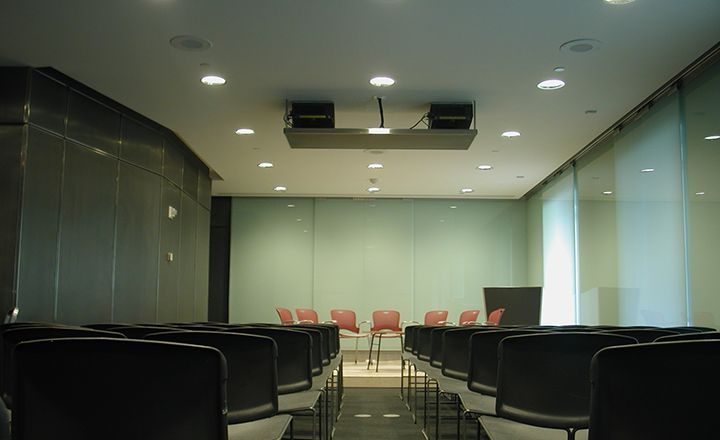 an empty room with chairs on a stage and chairs arranged in rows for the audience.