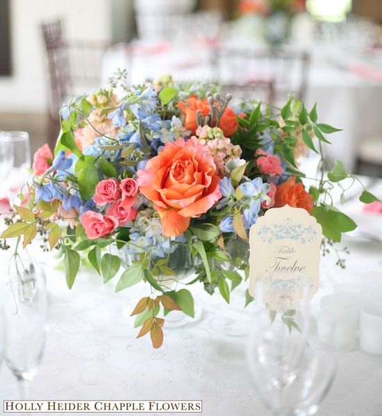 Pretty, tabletop centerpiece of roses, spray roses, delphinium, and foliage.  Gorgeous shades of pink, apricot, light blue, and green.
