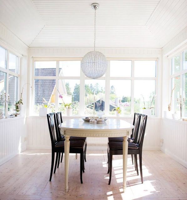 Bright White Sunroom With An Oval Gustavian Table Dark Wood Dining Chairs And A Crystal Ball Chandelier