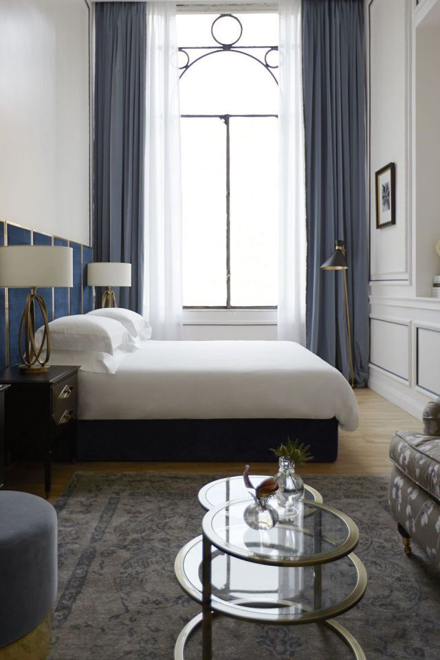 Before it was a hotel, Rome's Palazzo Dama belonged to the aristocratic Malaspina family. While the villa's decor has been updated in rich shades of blue, the original architecture inspired the design of each room. In the junior suite seen here, the circular window details are echoed throughout the rest of the interior, from the bedside lamps to the coffee table.