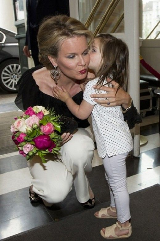 Princess Mathilde of Belgium received flowers and a kiss from a child as she arrives for a royal visit to the opera 'Cosi Fan Tutte', at the Munt Schouwburg - Theatre in Brussels, 11 June 2013