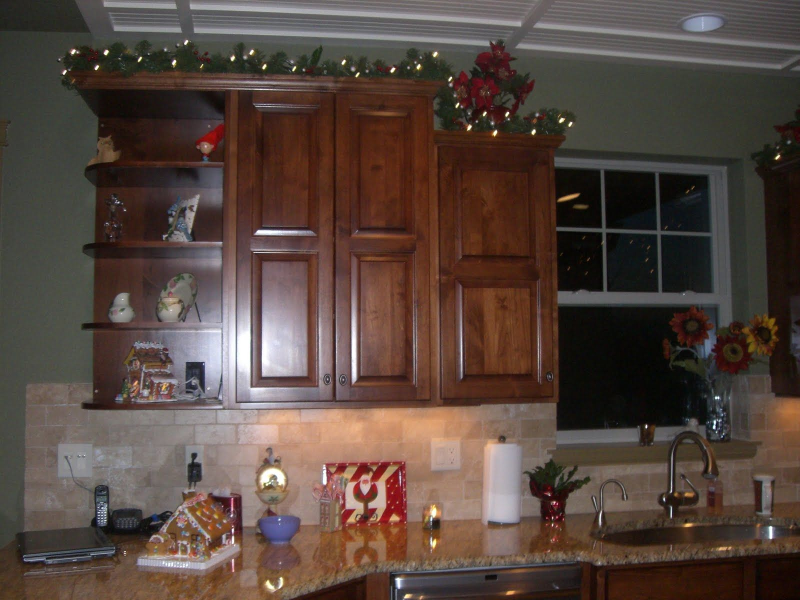 love this idea i have lights and grapes up there now but migtht try the garland lights idea on kitchen cabinets xmas decor id=60833