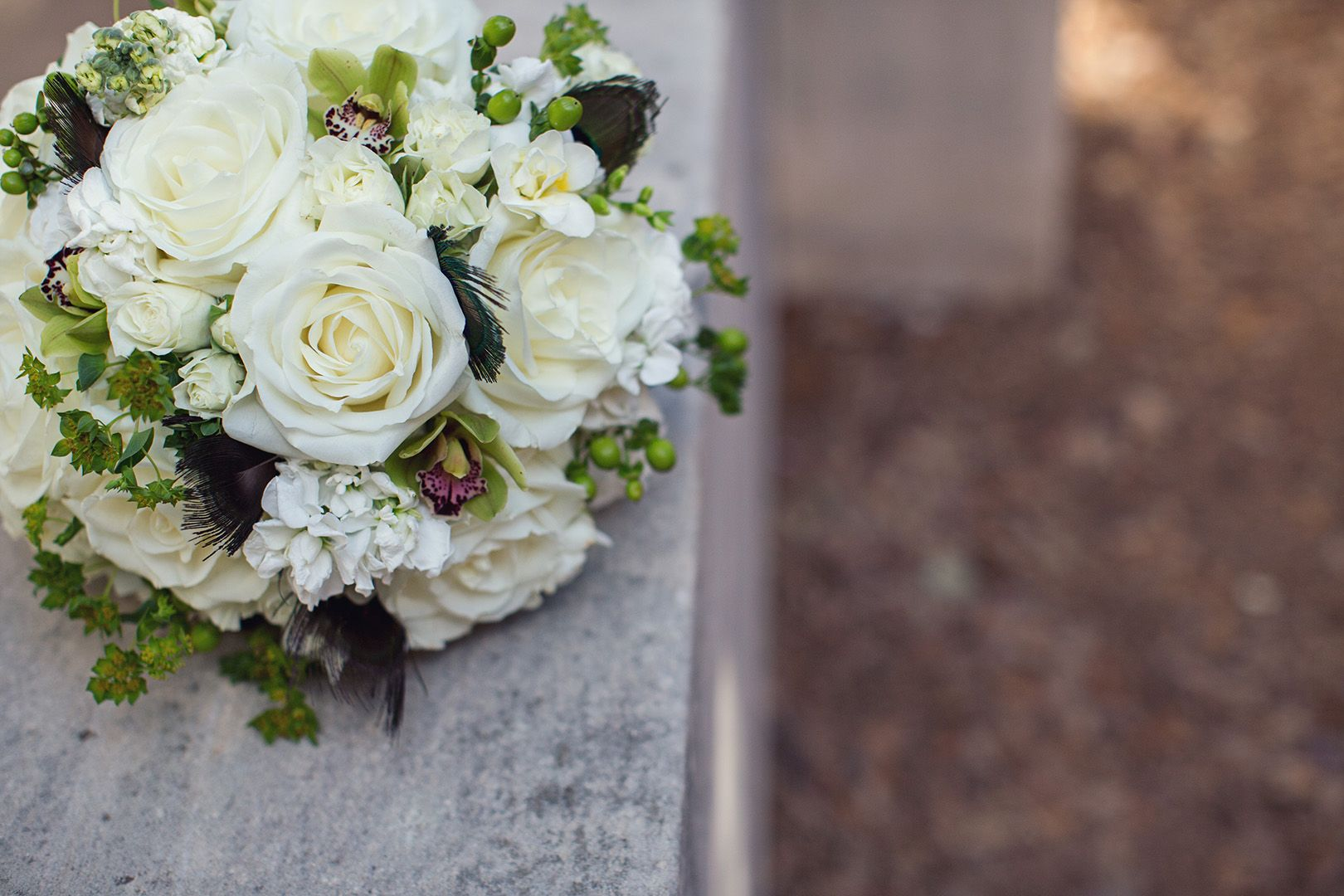 White bouquet with peacock feathers by Bouquets of Austin. Photo by Caroline Fontenot Photography.
