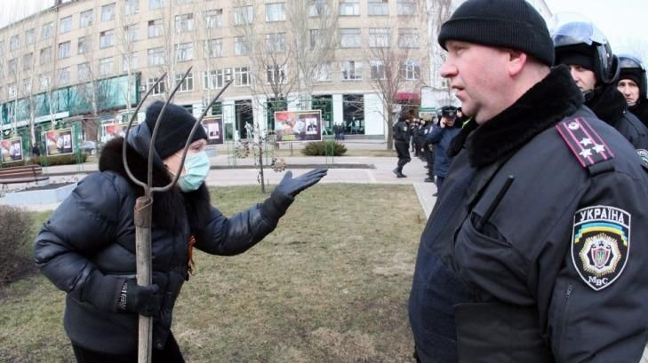 A supporter of ousted president Viktor Yanukovych tries to reach anti-government protesters celebrating victory in the industrial city of Donetsk.