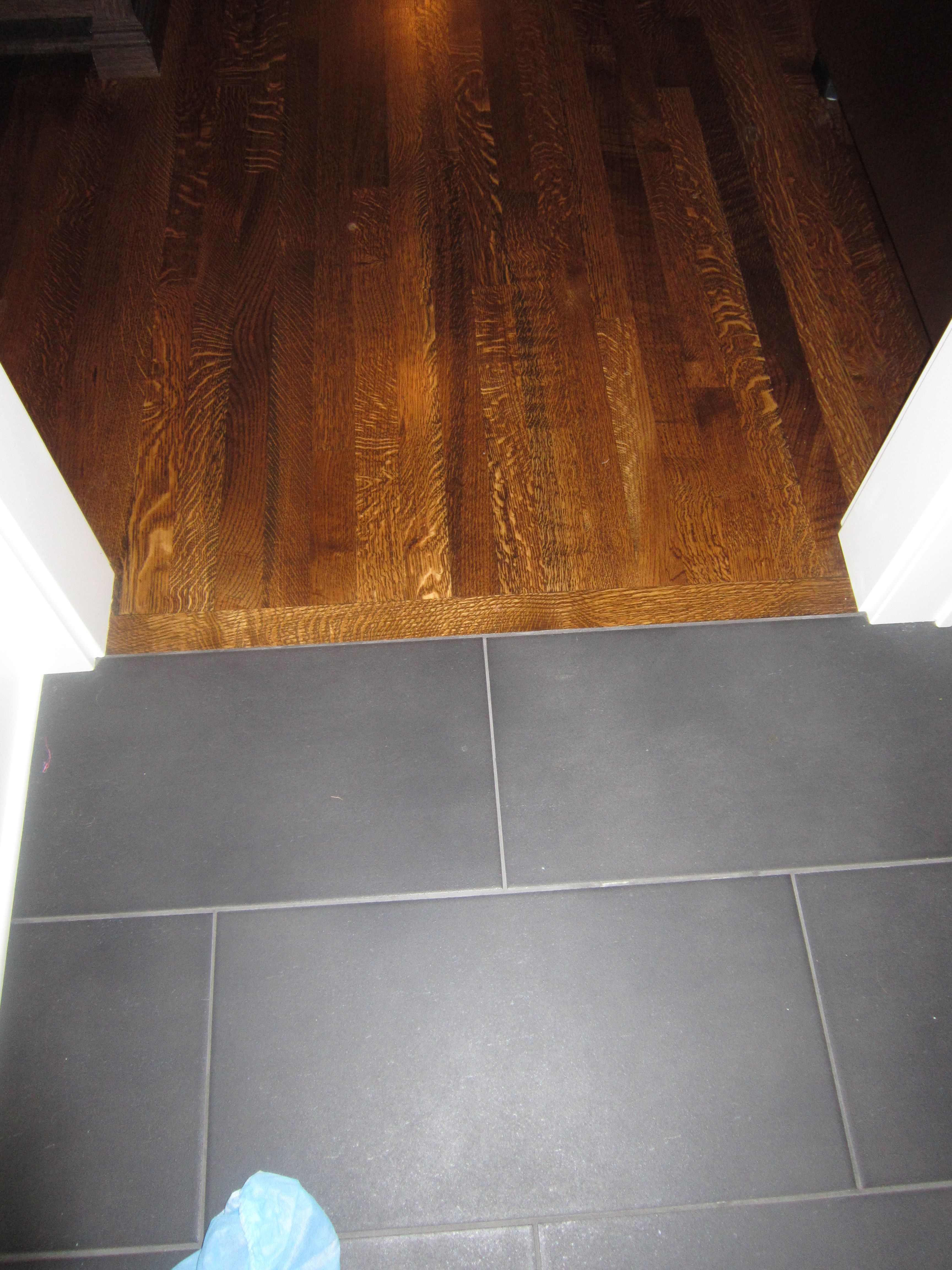 Like the dark grey tile in the mudroom and how it looks against a dark wood stain.