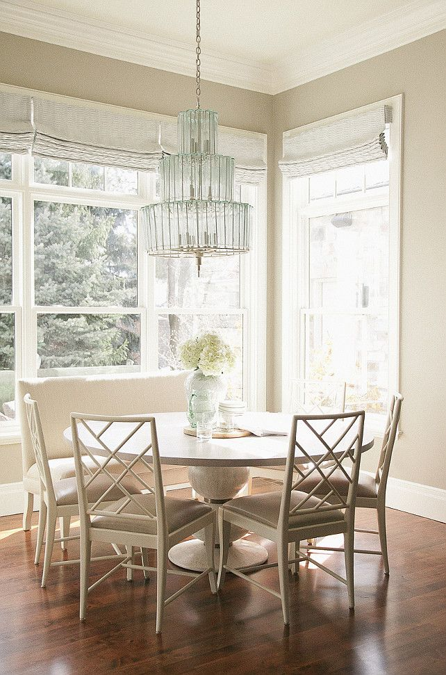 Chic monochromatic breakfast room features a turquoise