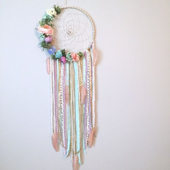 I just love the soft, fresh feel of this feminine, pastel dreamcatcher!! The base is wrapped in white/gold yarn with a cream twine hand woven authentic web holding 2 specialty flower beads. There is greenery and flowers in the colors peachy pink, cream, pastel blues, pastel teals,