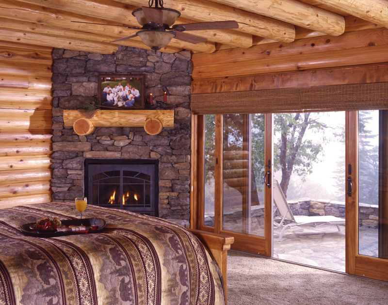 This is nice log cabin bedroom with a fireplace and a for Log cabin fireplaces pictures