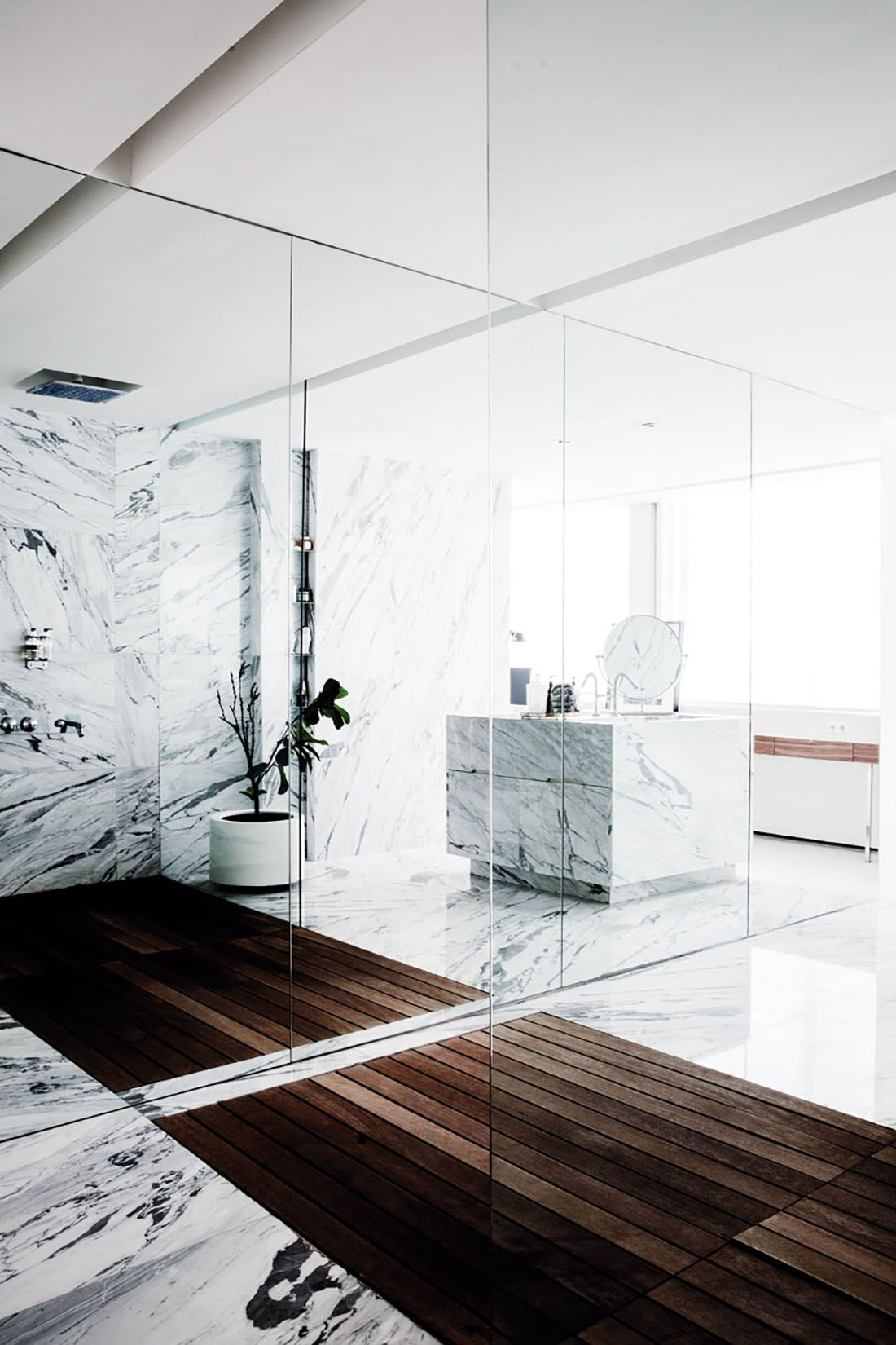 Bright white marble contrasts with rich wood flooring bathrooms