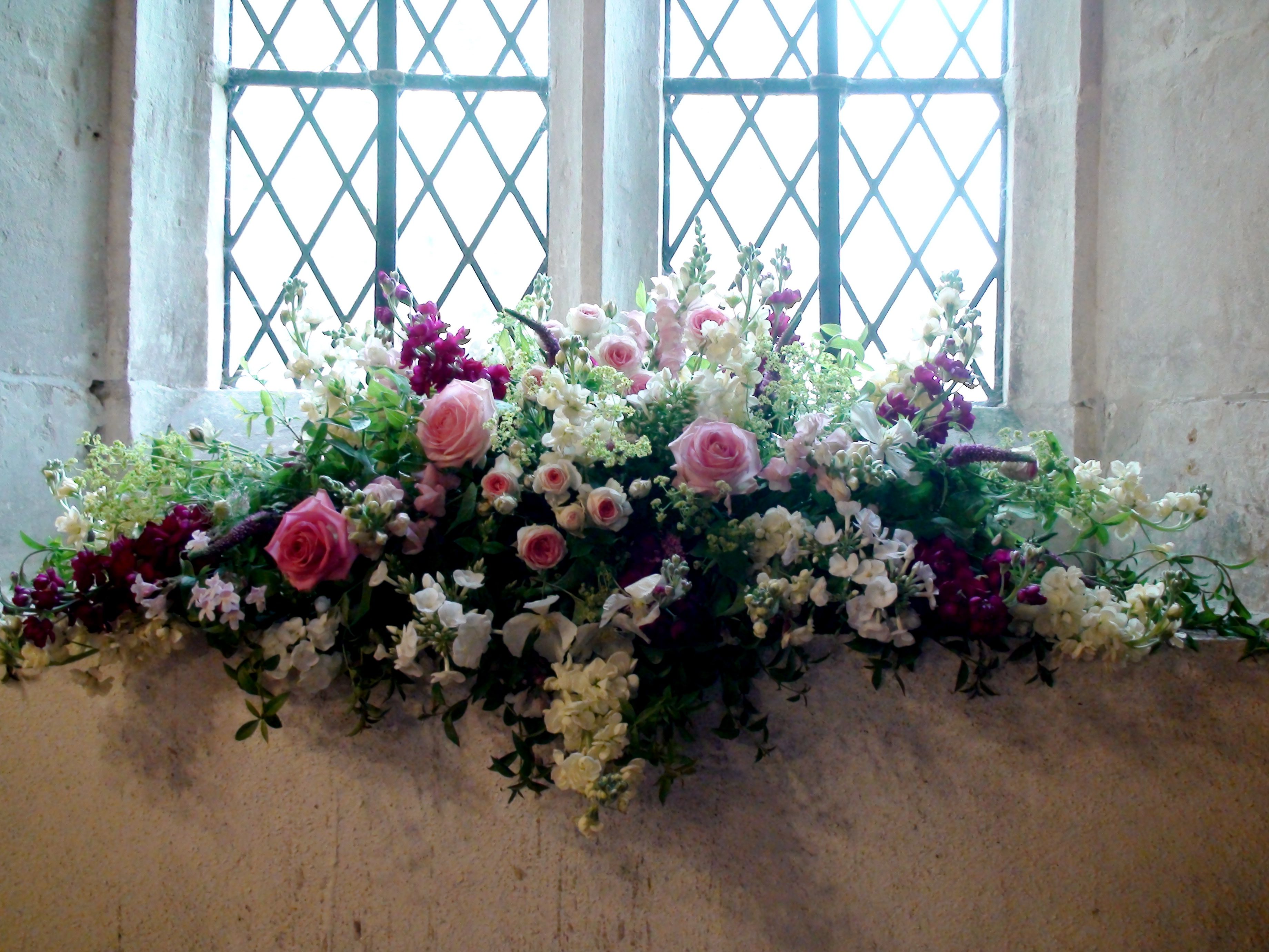 A Pretty Arrangement For A Church Windowsill With Roses Stocks
