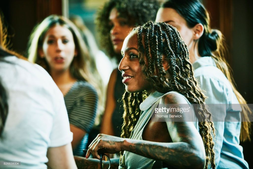 Stock Photo Smiling woman in discussion with friends in