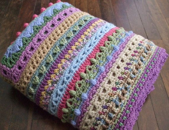 This striped afghan is a sampler of different crochet stitches. It is crocheted using random scraps of yarn to make a very colorful afghan.    It measures approximately 56 square.    It is made out of a variety of different colors and acrylic yarns, mostly Red Heart.    Machine washable and dryable.
