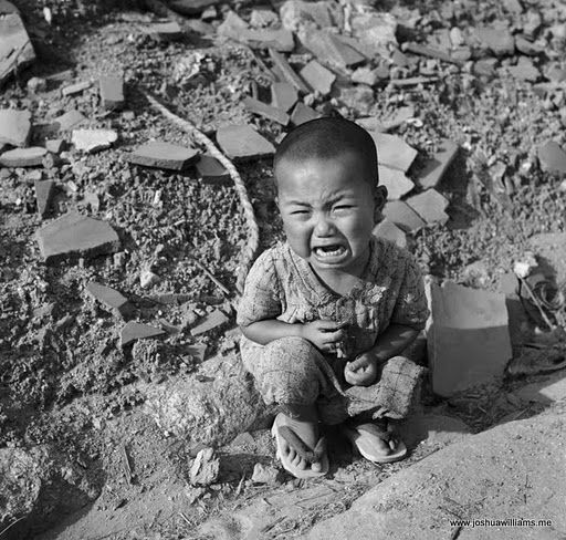 Young Japanese Boy Crying While Sitting Alone In Rubble In The