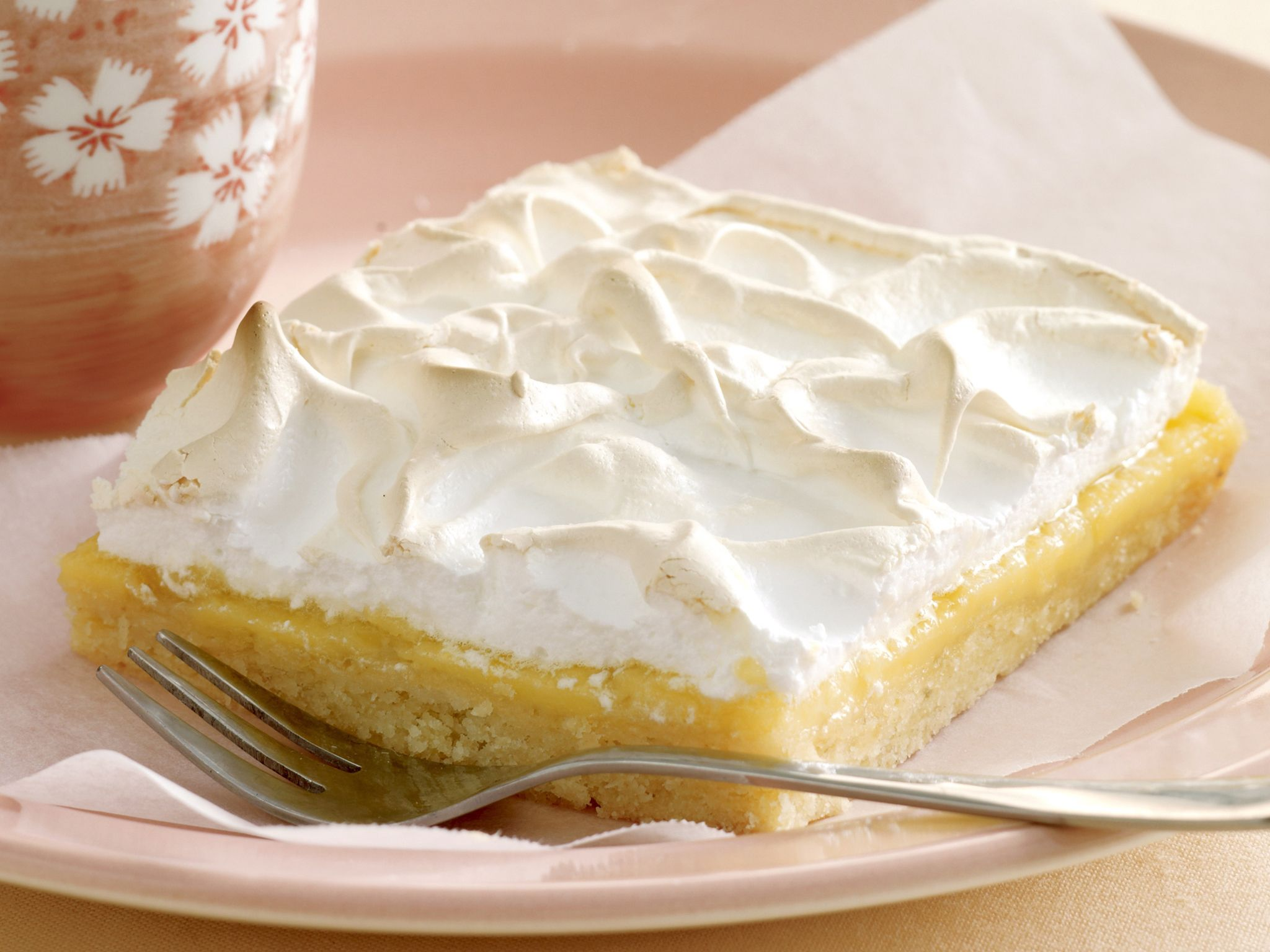 Indulge in tangy lemon and fluffy meringue on a buttery, biscuity base for a deliciously zesty sweet treat.