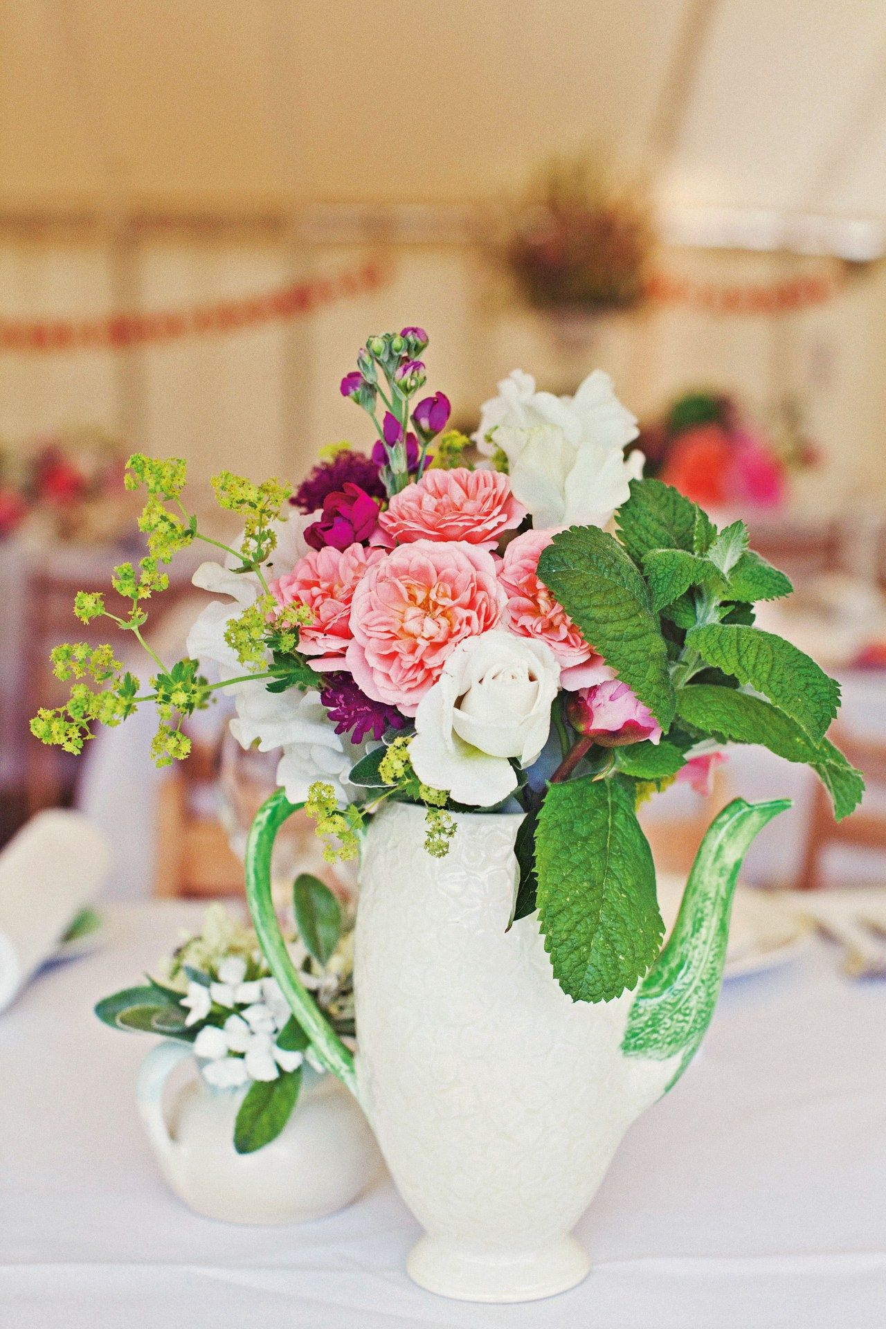 Mixed roses, mint, alchemilla mollis, gladioli and scabious arranged in a vintage china teapot.
