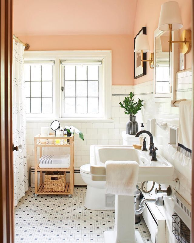 Photo of peachy pink bathroom white wainscotting white pedestal sink white and black tile…