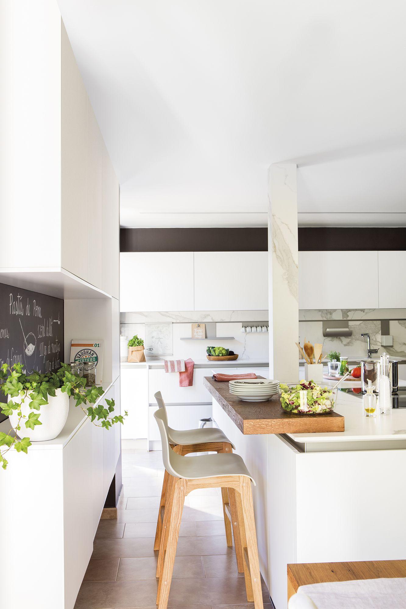 Cocina blanca con isla barra de madera taburetes y for Sillas de cocina blancas de madera