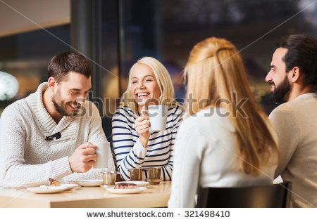 people, leisure and communication concept - happy friends meeting and drinking tea or coffee at cafe
